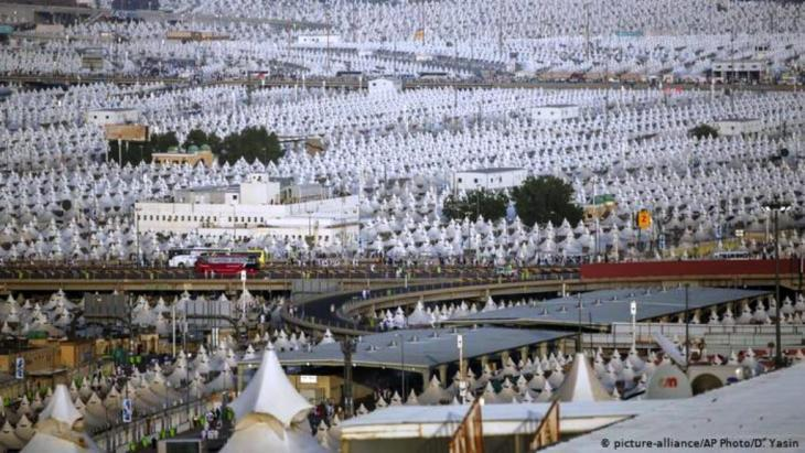 Muslim pilgrims walk back to their tents during the annual hajj pilgrimage on the first day of Eid al-Adha in Mina, 2018 (photo: picture-alliance/AP/D. Yasin)