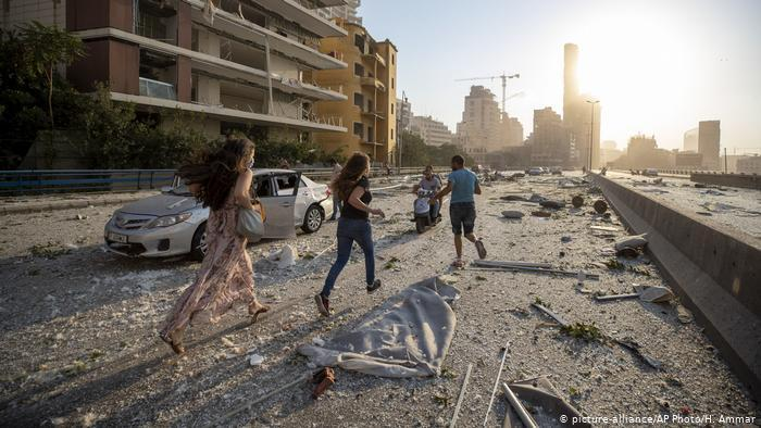 People in Beirut run through rubble in the explosion aftermath (photo: picture-alliance/AP Photo/H. Ammar)
