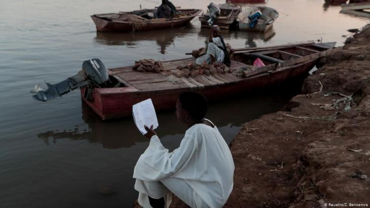 A high school student reads his lesson notes as he sits by a bank on the Nile river in Alqamayir, Omdurman, Sudan, 15 February 2020 (photo: REUTERS/Zohra Bensemra)