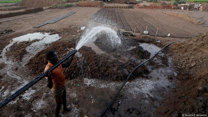 Zaki El-Dine, 24, a brick-maker, pours water from the Nile river onto a patch of mud to make bricks on Tuti Island, Khartoum, Sudan, 12 February 2020 (photo: REUTERS/Zohra Bensemra)