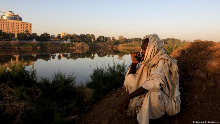 Mohamed Ahmed al Ameen, 55, a brick maker, drinks a cup of tea as he sits on the edge of the Blue Nile near an open-air factory on Tuti Island, Khartoum, Sudan, 14 February 2020 (photo: REUTERS/Zohra Bensemra)
