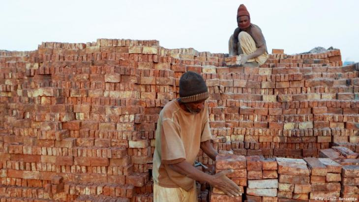 Mustapha, 60, a brick maker, piles up bricks after removing them from a kiln at an open-air factory on Tuti Island, Khartoum, Sudan, 20 February 2020 (photo: REUTERS/Zohra Bensemra)