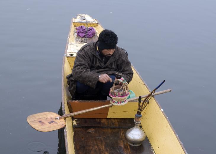 A boatman warms his hands on Lake Dal, Kashmir (photo: Sugato Mukherjee)