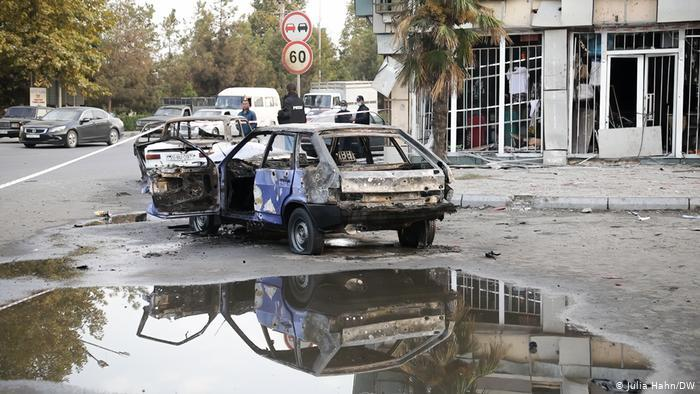 A burned-out car in front of a building with a shop that has been destroyed in Barda (photo: Julia Hahn/DW)
