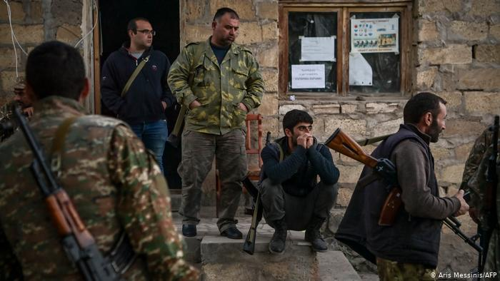 Several men, some wearing camouflage shirts, squatting and standing in front of a building in Stepanakert (photo: Aris Messinis/AFP)