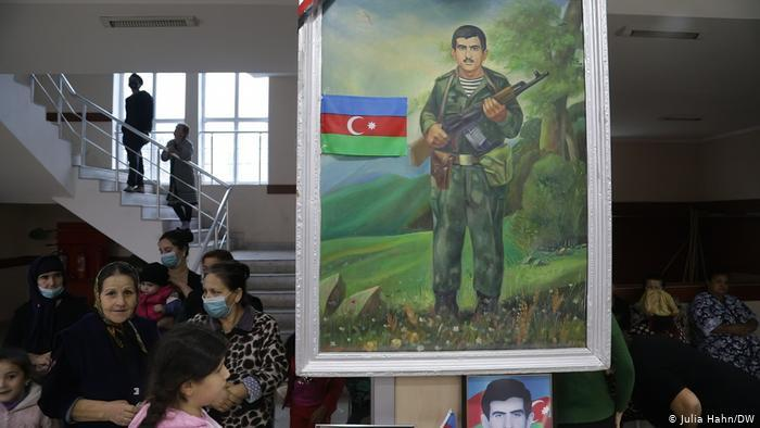 Women and children in a room and a large painting of a soldier (photo: Julia Hahn/DW)