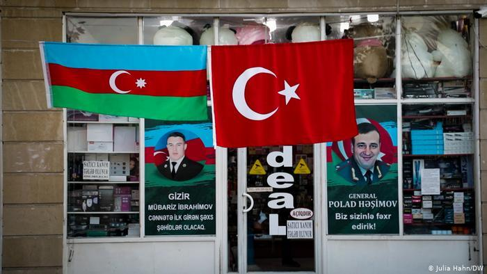 Turkish and Azerbaijani flags in front of a business with propaganda posters in the windows (photo: Julia Hahn/DW)