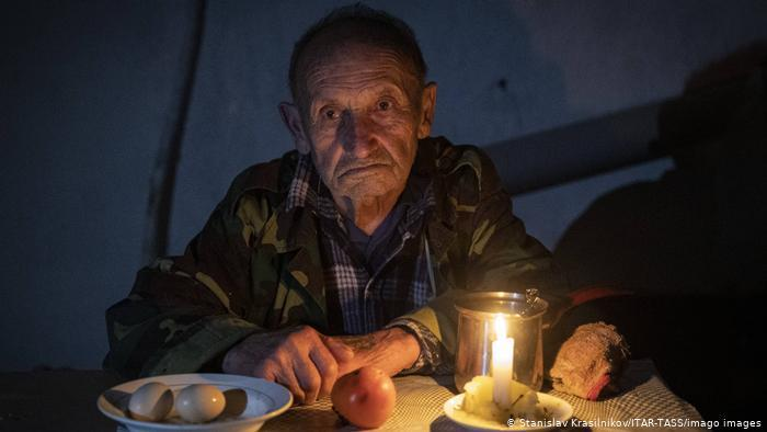 An elderly man in the dark, seated a table with a lit candle and plates with boiled eggs, a tomato, bread (photo: Stanislav Krasilnikov/ITAR-TASS/imago images)