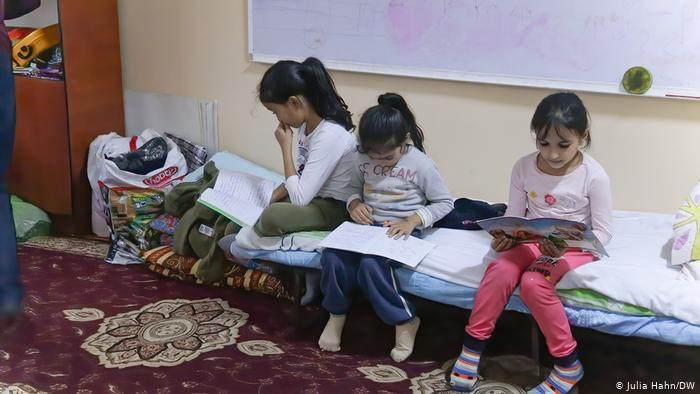 Three young girls seated on a cot, reading, in the Azerbaijani town of Barda (photo: Julia Hahn/DW)