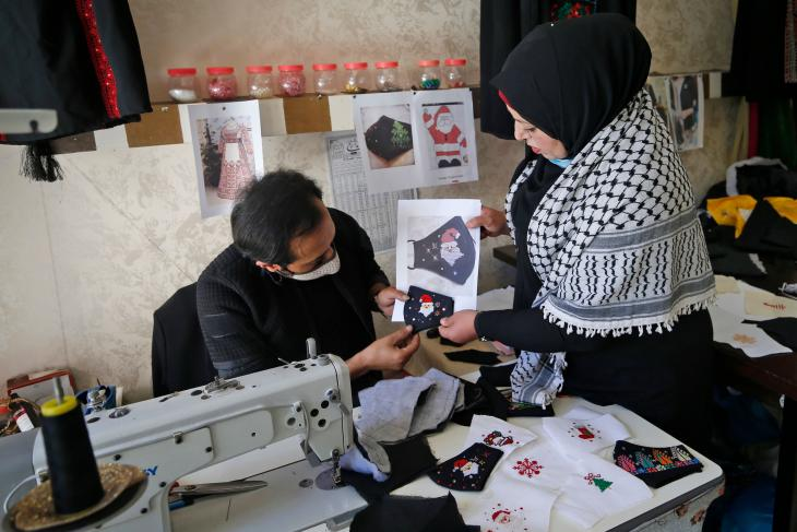 Owner of the workshop Suhad Saidam (right) discusses designs (photo: Mohammed Abed/AFP/Getty Images)