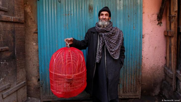 Fatih, 70, holds a cage of partridges as he poses for a picture at Ka Faroshi bird market in Kabul, Afghanistan (photo: REUTERS/Mohammad Ismail)
