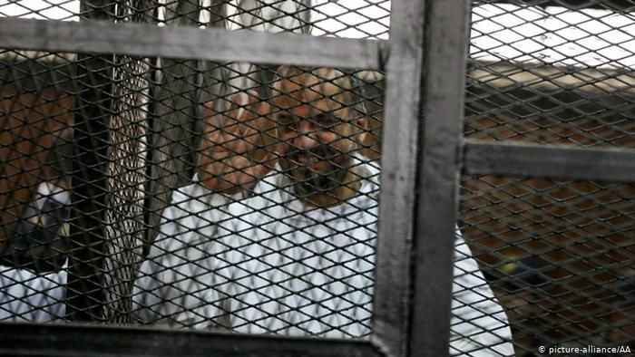 Mohammed el-Beltagy waves from behind bars during his trial in 2014