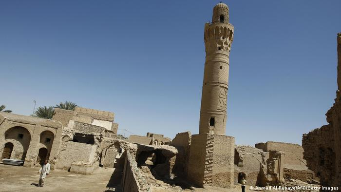 Minaret in front of old stone buildings