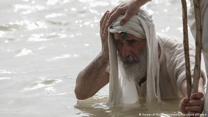 A person puts a hand on the head of an old man with a cloth on his head and holding onto a wooden stick, standing chest-deep in water
