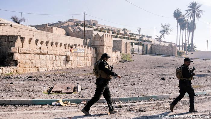 Soldiers with rifles patrol in front of the ruins of the Jonah shrine
