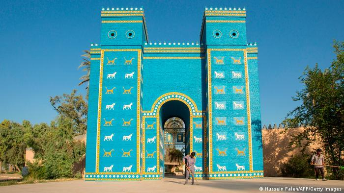 Large turquoise-coloured gate with gold and white decorations, person in front