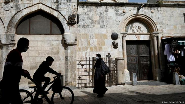 People pass two Stations of the Cross along the route of the Via Dolorosa in Jerusalem's Old City, 21 March 2021 (photo: Reuters/Amir Cohen)