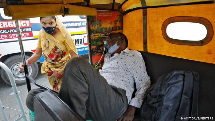 A patient wearing an oxygen mask waits inside an auto rickshaw to enter a COVID-19 hospital for treatment