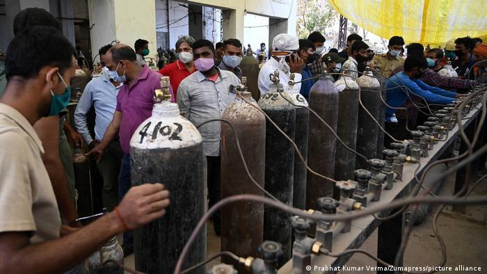 Family members of COVID-19 patients queue to take cylinders filled with medicated oxygen