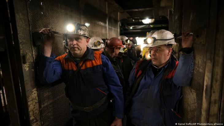Bosnian coal miners hold bags of food as they stand in an elevator taking them underground at a mine in Zenica, Bosnia, 29 April 2021 (photo: AP Photo/Kemal Softic)