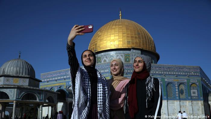 Women pose for a selfie in front of the Dome of the Rock