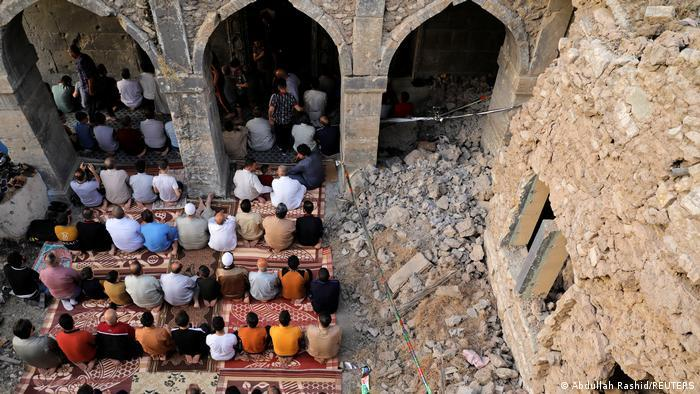 People pray next to the ruins of Al-Masfi mosque in Mosul, Iraq