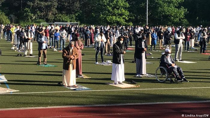 Muslims pray on a sports field in Bonn while keeping their distance and wearing masks