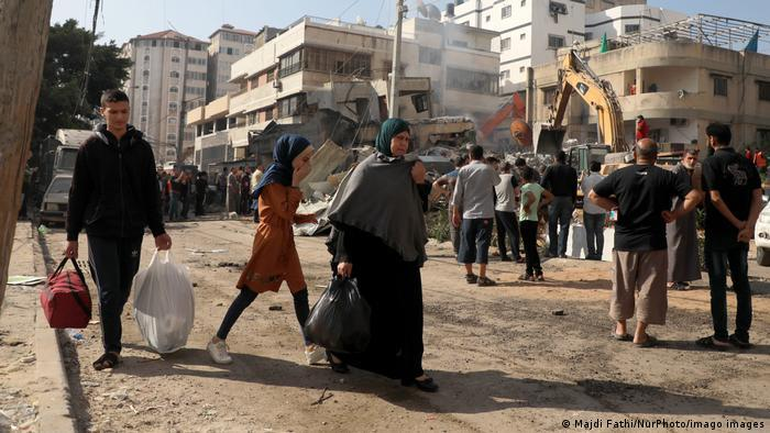 People move about Gaza with bags of belongings as crowds watch tractors clearing rubble