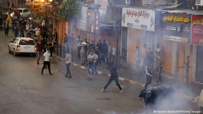 Smoke over a street with many men; one masked man gets ready to hurl an object