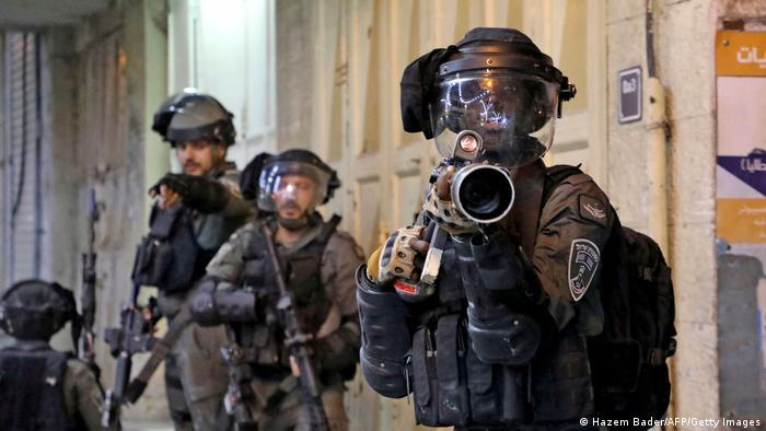 Israeli security forces position themselves against demonstrators with heavy weaponry