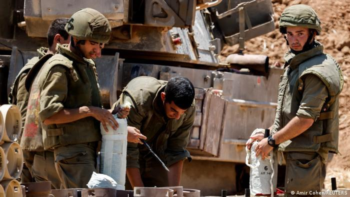 Israeli soldiers check artillery shells in an area near the border with Gaza