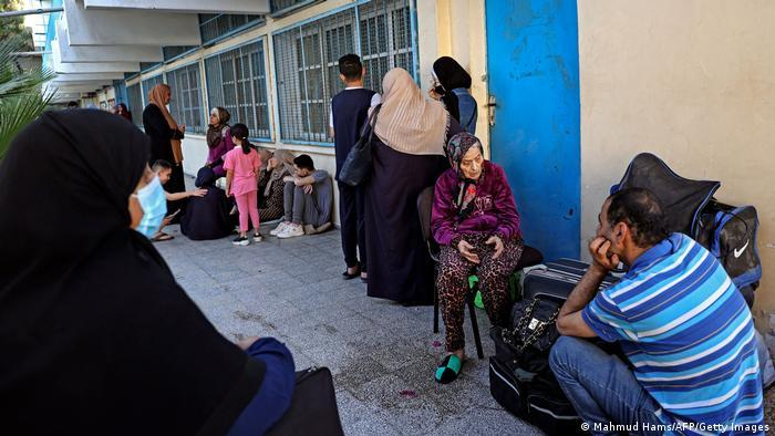 People of all ages sit in front of the UN building in Gaza city