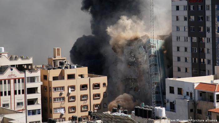 Smoke rises as a building falls after an Israeli airstrike in Gaza