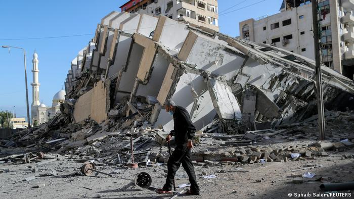 A man with a walking stick passes by a destroyed building
