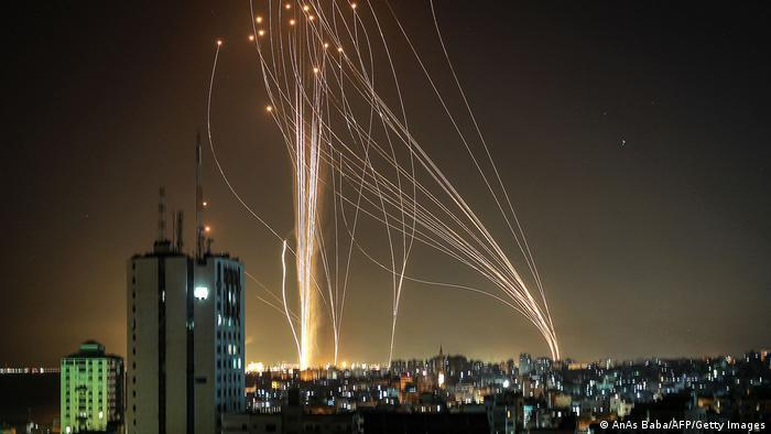 Dozens of rockets rise into the air in a long exposure that lets them be seen over Tel Aviv