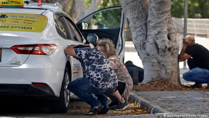 Three people duck behind a car and under a tree, covering their heads with their hands