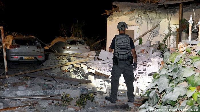 An Israeli soldier stands in the rubble of a building