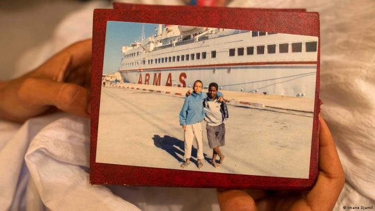Maatoug holds a photo taken in 2008 of himself and a friend posing in front of The Armas Essalama (photo: Imane Djamil)