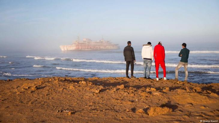 Hassan Boulahcen, 27, a surf coach, Maatoug, Hossin Ofan, 34, Nuevas Olas surf club general coordinator, and Oussama Segari, 26, who works as the club's treasurer and coffee shop manager, face the sea in front of the Armas shipwreck (photo: Imane Djamil)