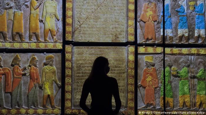 A museum staff member in shadow looks at a colour projection ahead of the 'Epic iran' exhibition