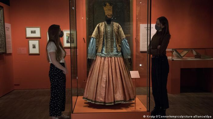 Museum staff members looks at a woman's jacket, blouse and skirt from 1840-50, on show ahead of the Epic Iran exhibition