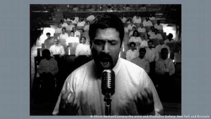 Black and white image of a man in front of a microphone with people in the background; an excerpt from Turbulent by Shirin Neshat as part of the Epic Iran exhibition