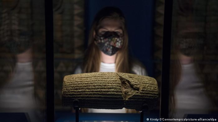 A museum staff member looks at the Cyrus Cylinder in a display case ahead of the 'Epic Iran' exhibition