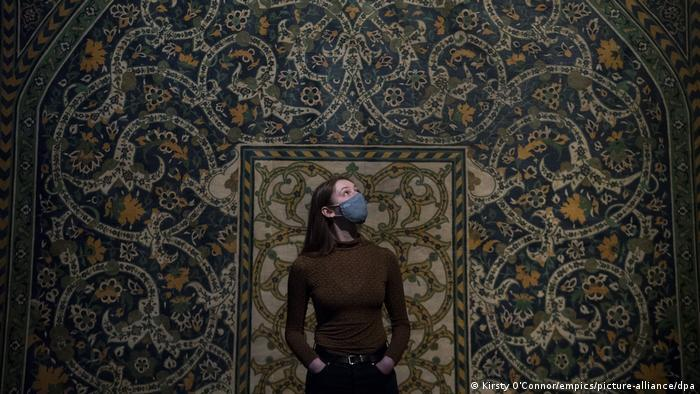 A museum staff member standing in front of a full-size reproduction of a tilework from 1877 at the 'Epic Iran' show at the V&A in London