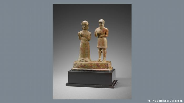 A bronze casting showing two figures with their hands clasped in prayer