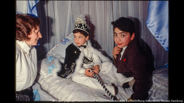 A boy in festive clothes at his circumcision party, with another boy and a woman next to him