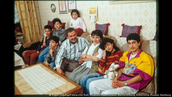 A family of eight sitting on a sofa