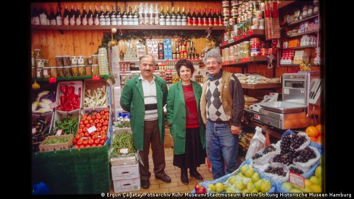 Three people standing in a grocery store and smiling into the camera