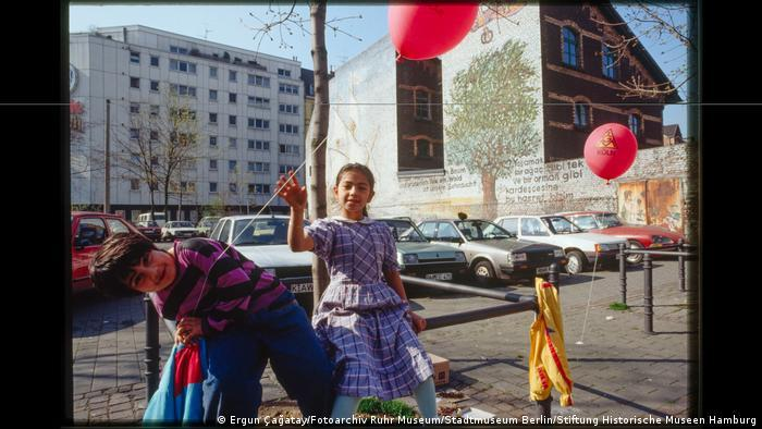 Two children with balloons in front of a parking lot