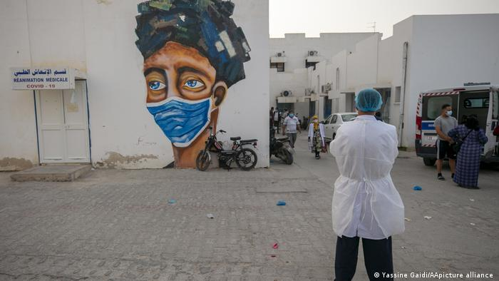Person wearing a white lab coat and a green surgical cap watches some people walk among square white buildings, one with a large graffiti of a face with a mask (photo: Yassine Gaidi/AA/picture-alliance)